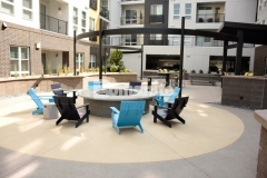 The hardscape surface around the firepit lounge area at COLAB was created using Bomanite Exposed Aggregate Sandscape Refined decorative concrete that was placed in alternating colors and incorporated amber glass and crushed mirror glass to provide beautiful reflection and a stunning design.