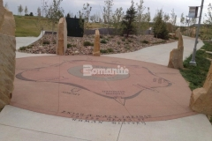 The sandblasted graphics and text that display informational content throughout Centennial Center Park are featured on a Bomanite Sandscape Texture decorative concrete hardscape, which offers a beautiful architectural finish with consistent texture and durability.