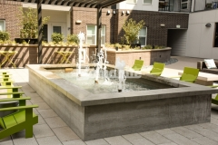 A board-forming technique was used here to imprint wood grain onto the concrete, visually softening and creating warmth on the surface of this stunning water feature and enhancing the stylish gathering space at the COLAB Co-Housing Development.