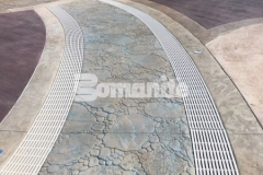 This hardscape surface at Canobie Lake Park was created using Bomanite Imprint Systems and includes serpentine drains that infiltrate storm water and minimize runoff while accentuating the decorative concrete decking at the Castaway Island water feature.