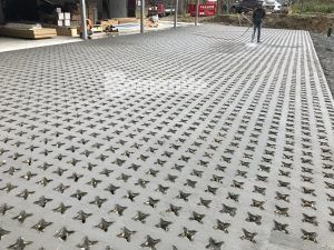 Grasscrete Pervious Concrete is biodegradable and environmentally friendly and a crew member pressure washes the project after the voids are created to initiate that process.