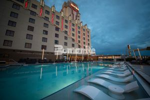 Long view with lounge chairs in the pool at the Hard Rock Casino located in Tulsa, OK, with Bomanite Exposed Aggregate Alloy decorative concrete installed on the pool deck by Bomanite of Tulsa.