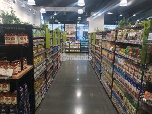 Long view of grocery aisle, with shelves on either side, at Brothers Marketplace in Waltham, MA, featuring Bomanite Systems Custom Polished VitraFlor decorative concrete flooring installed by Premier Concrete Construction.